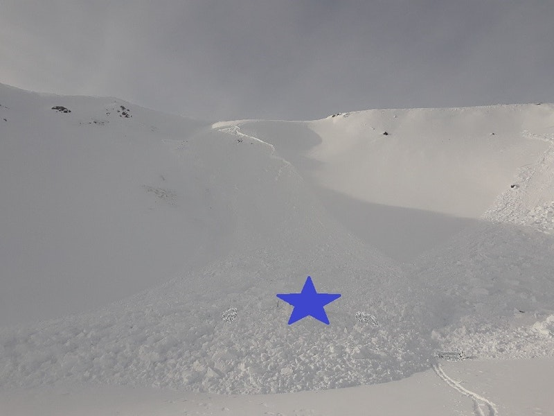 <b>Figure 6:</b> Looking to the northwest from the toe of the debris. The first avalanche triggered by the group is partially visible on the right side of the image. The avalanche in the center of the image is the second avalanche triggered by the group (remote trigger). The blue star represents the burial site. (<a href=javascript:void(0); onClick=win=window.open('https://caic-production.imgix.net/0bd84amy1auywa4awu00i2depa5u?ixlib=php-3.1.0&s=6386eb085ee382db855b8162c6ef35a1','caic_media','resizable=1,height=820,width=840,scrollbars=yes');win.focus();return false;>see full sized image</a>)