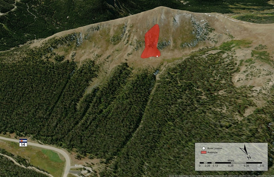 <b>Figure 2:</b> An overview of the accident site on Diamond Peaks, Cameron Pass, in the Front Range zone. The red area shows the approximate boundary of the avalanche. The white point near the bottom right corner is where Skier 2 was buried. The Cameron Pass parking area is the loop at the bottom of the image, just off CO State Highway 14. The skiers ascended the obvious gully through the trees to the right of the parking area. From there they skinned right through the thin trees to the saddle between the south summit of Diamond Peaks and the northern summit, which is off the image to the right. They followed the ridgeline to the south. Skier 1 descended first and stopped near the cliff band pictured above and to the left of the avalanche. Skier 2 triggered the avalanche approximately 150 feet below near the top of the gully. She was carried down the gully and buried in a standing position. (<a href=javascript:void(0); onClick=win=window.open('https://caic-production.imgix.net/63lqy3uxax3h68vzairypl4fl778?ixlib=php-3.1.0&s=1c62367263f2fdbb2b2d839cc45405d4','caic_media','resizable=1,height=820,width=840,scrollbars=yes');win.focus();return false;>see full sized image</a>)