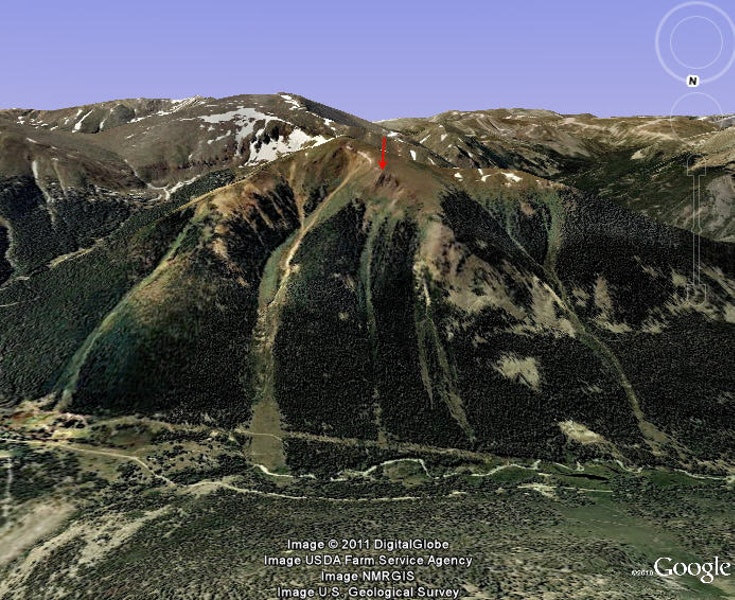 <b>Figure 6:</b> A Google Earth image of the area. The Corkscrew avalanche path is the large path the starts near the summit of Morgan Peak. The avalanche started below the arrow. You can see the power line swath through the trees near the base of the drainage. (<a href=javascript:void(0); onClick=win=window.open('https://caic-production.imgix.net/7hjdskpnkw5gzbbphtlcgjfbfc9c?ixlib=php-3.1.0&s=1329d4c5d71c55eb18d798888e706c56','caic_media','resizable=1,height=820,width=840,scrollbars=yes');win.focus();return false;>see full sized image</a>)