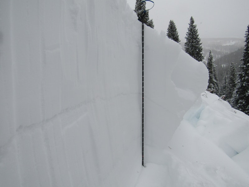 <b>Figure 6:</b> Looking across the crown face of the avalanche. The melt-freeze crust is the prominent narrow layer in the middle of the wall. (<a href=javascript:void(0); onClick=win=window.open('https://caic-production.imgix.net/8ivzs1rb5irf6ch1yyepm3mhfq7d?ixlib=php-3.1.0&s=35bcc9bd9b34b719dedc7543f3051be9','caic_media','resizable=1,height=820,width=840,scrollbars=yes');win.focus();return false;>see full sized image</a>)