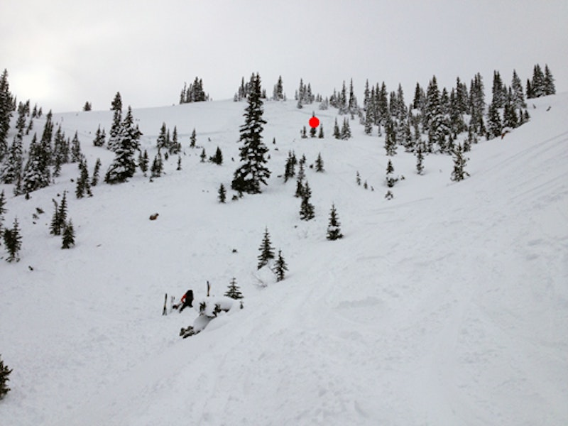 <b>Figure 2:</b> Overview of the unintentionally-triggered slide in McFarlane's Bowl, Richmond Ridge, 1-1-15. The injured skier is being attended to in the lower left of the image. He triggered the slide near the red dot and was strained through the trees. (<a href=javascript:void(0); onClick=win=window.open('https://caic-production.imgix.net/acpbf951ymdjih6h3s8tt4rurarx?ixlib=php-3.1.0&s=26ca489c836d03bce3b1e171ad7bce34','caic_media','resizable=1,height=820,width=840,scrollbars=yes');win.focus();return false;>see full sized image</a>)