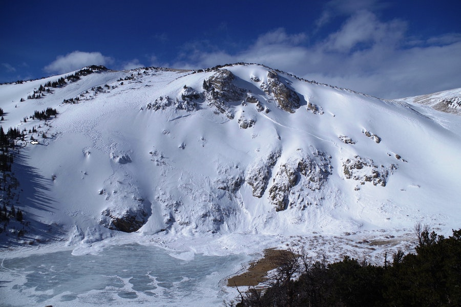 <b>Figure 1:</b> Overview of St Marys Lake avalanche 1/16/2016. The white arrow shows the location of a snowpit completed by CAIC forecasters on 1/18/2016. Picture taken on 1/18/2016 from Fox Mountain, courtesy Dale Atkins. (<a href=javascript:void(0); onClick=win=window.open('https://caic-production.imgix.net/b125f5yamwlirxyj849c8de4au1v?ixlib=php-3.1.0&s=abcb86dcaf4465edf01fc7563934bf72','caic_media','resizable=1,height=820,width=840,scrollbars=yes');win.focus();return false;>see full sized image</a>)