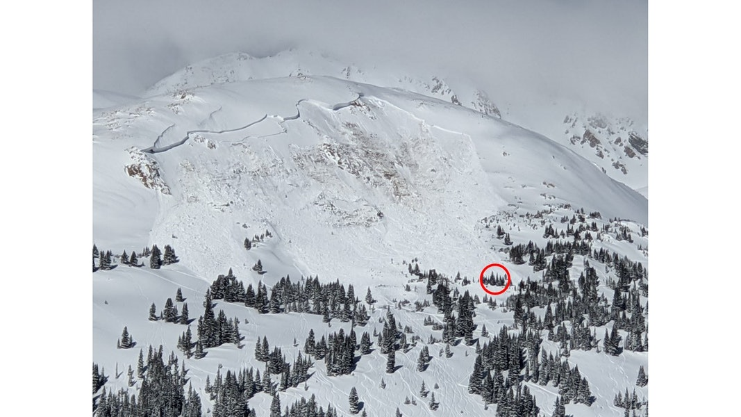 <b>Figure 3:</b> A photo of the avalanche taken on February 14, 2021. The red circle indicated where the avalanche buried Rider 2. (<a href=javascript:void(0); onClick=win=window.open('https://caic-production.imgix.net/d9h8qn7kab0aoed23b67svhn1h8o?ixlib=php-3.1.0&s=fa639febb552154d6cd79b1b951e069d','caic_media','resizable=1,height=820,width=840,scrollbars=yes');win.focus();return false;>see full sized image</a>)