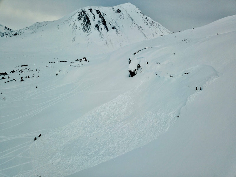 <b>Figure 1:</b> View of avalanche looking to the north. The snowmachines and people are investigating the site. (<a href=javascript:void(0); onClick=win=window.open('https://caic-production.imgix.net/gcgrszmrpczak1u1qlf4mntzk7rp?ixlib=php-3.1.0&s=f57eca880e7a489c26b80798bfd3f3e7','caic_media','resizable=1,height=820,width=840,scrollbars=yes');win.focus();return false;>see full sized image</a>)