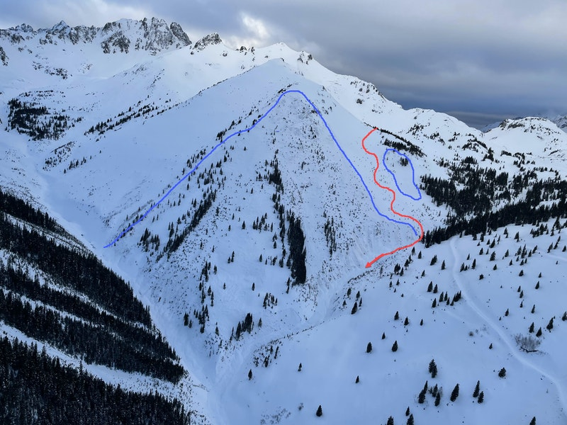 <b>Figure 1:</b> An overview of the accident site. The red line marks the general path of the group, down the slope and then down the gully. The blue lines mark the approximate boundaries of the avalanche. The large avalanche on the left caught the group of skiers. The small avalanche on the right released sympathetically. (Image courtesy of Telluride Helitrax) (<a href=javascript:void(0); onClick=win=window.open('https://caic-production.imgix.net/hbbpfi7kmbsi7w3d395mr4ocrpih?ixlib=php-3.1.0&s=9ea81e7beca9ecb5568cf475f611b088','caic_media','resizable=1,height=820,width=840,scrollbars=yes');win.focus();return false;>see full sized image</a>)