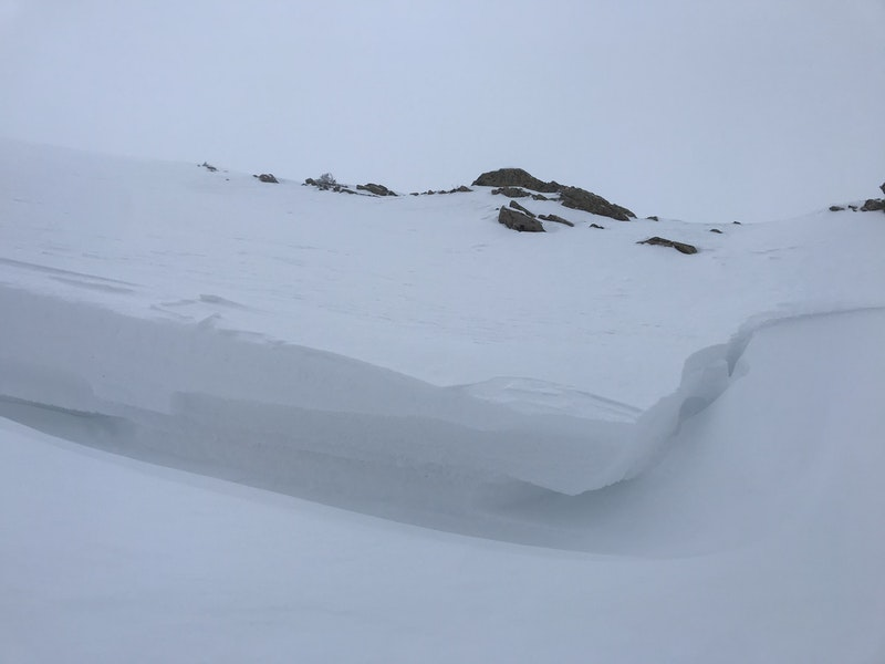 <b>Figure 6:</b> A closer look at the crown face. The top slab is visible jutting over the weak layer just below. The slab was hard wind-drifted snow and the weak layer was composed of faceted crystals. (<a href=javascript:void(0); onClick=win=window.open('https://caic-production.imgix.net/ludnt1kew38ad9wrfdlzw6ppa7bz?ixlib=php-3.1.0&s=2c1352fa36e07a192a0f1c5e6ad67443','caic_media','resizable=1,height=820,width=840,scrollbars=yes');win.focus();return false;>see full sized image</a>)