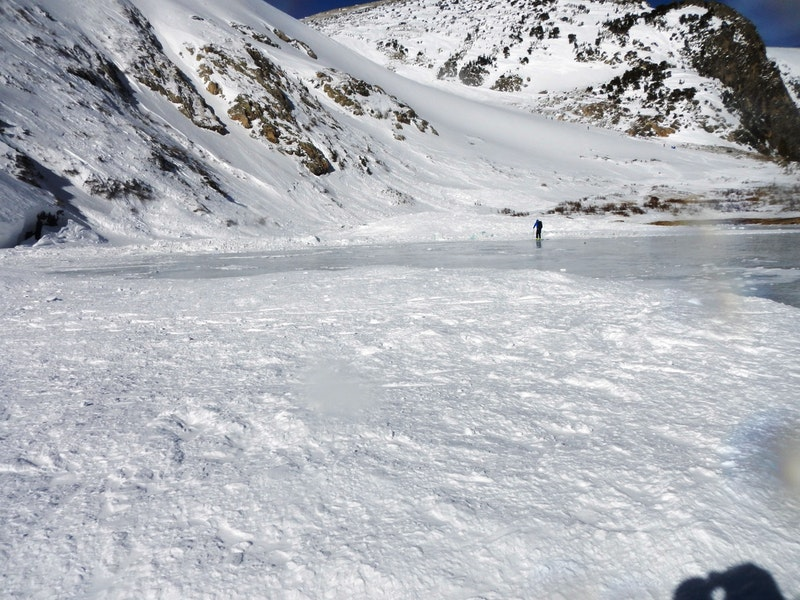 <b>Figure 10:</b> Looking north along the lake with debris lobes spread onto the ice. Deepest debris was on the north end. (<a href=javascript:void(0); onClick=win=window.open('https://caic-production.imgix.net/mebesb61xjc28744dosbkx3fue4n?ixlib=php-3.1.0&s=8c304dce178b5712e0b3df7e15a1157c','caic_media','resizable=1,height=820,width=840,scrollbars=yes');win.focus();return false;>see full sized image</a>)