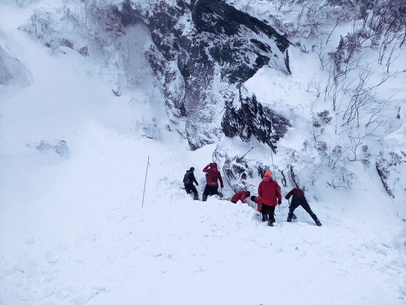<b>Figure 5:</b> Rescuers digging down to enable an avalanche probe to reach and precisely locate Forgays. Note the narrow strip of debris adjacent to the rocks with no debris to the left of the rescuers. (<a href=javascript:void(0); onClick=win=window.open('https://caic-production.imgix.net/n569l8r3tscivae0jfb0sdzbnn2d?ixlib=php-3.1.0&s=e8b81559f9575ef7129e9790f1639ded','caic_media','resizable=1,height=820,width=840,scrollbars=yes');win.focus();return false;>see full sized image</a>)