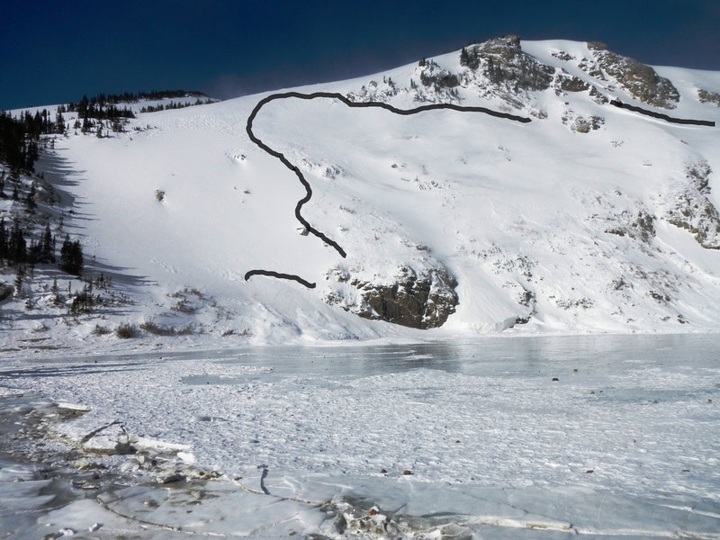<b>Figure 2:</b> South Flank of the avalanche. The black line highlights the fracture line. The climber was found on the looker's right side of the large rock in the center of the photo, buried at the edge of the lake ice. (<a href=javascript:void(0); onClick=win=window.open('https://caic-production.imgix.net/nqgjq6w1ocwxac65738gogodwygv?ixlib=php-3.1.0&s=939e1c44e4c31976c5ba34446c7e9b5e','caic_media','resizable=1,height=820,width=840,scrollbars=yes');win.focus();return false;>see full sized image</a>)