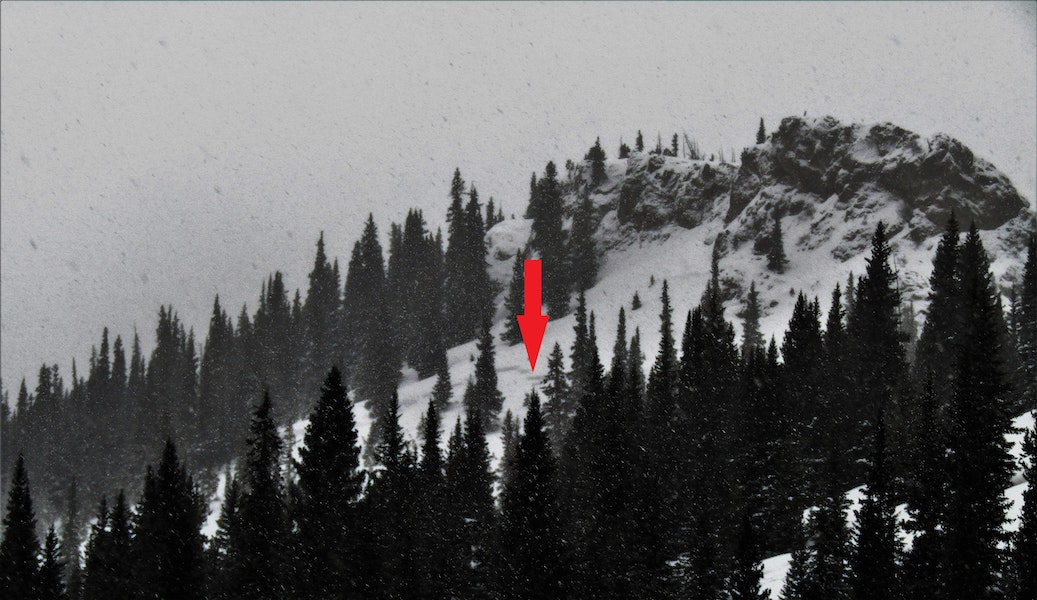 <b>Figure 2:</b> A distant image of the slope that avalanched. The red arrow points to the face of the crown.The skiers entered the slope to the left of the arrow, below the large rock outcrop. (<a href=javascript:void(0); onClick=win=window.open('https://caic-production.imgix.net/ntbgta870wm9o3w8p4z9l1oex4kj?ixlib=php-3.1.0&s=3f1451f8163d488f481598962eb0aaa5','caic_media','resizable=1,height=820,width=840,scrollbars=yes');win.focus();return false;>see full sized image</a>)