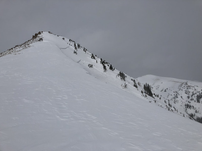 <b>Figure 6:</b> Looking north across the path. Notice the multiple crown faces. The top crown is most likely a wind slab. The lower crown broke on small facets and extends below the ridgeline in the lower right corner of the image. (<a href=javascript:void(0); onClick=win=window.open('https://caic-production.imgix.net/pn0yyu29tvtv12oksdcjel7gp3gv?ixlib=php-3.1.0&s=da33a9a6547e4455127e662e203abb24','caic_media','resizable=1,height=820,width=840,scrollbars=yes');win.focus();return false;>see full sized image</a>)