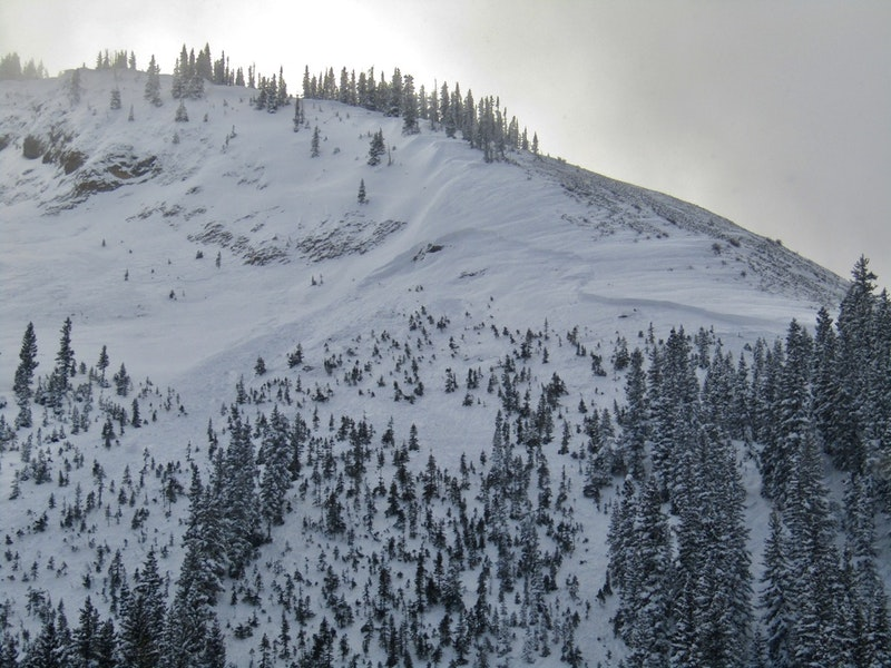 <b>Figure 2:</b> This image shows the crown of the avalanches in center right of the photo below the rocky ridge. The debris washed through the small sparse trees below. (<a href=javascript:void(0); onClick=win=window.open('https://caic-production.imgix.net/q7nr4wtwrqfgz74385rrz8slmrsc?ixlib=php-3.1.0&s=48c5b02d3b0a5c9c37558b8c6a7b26f9','caic_media','resizable=1,height=820,width=840,scrollbars=yes');win.focus();return false;>see full sized image</a>)