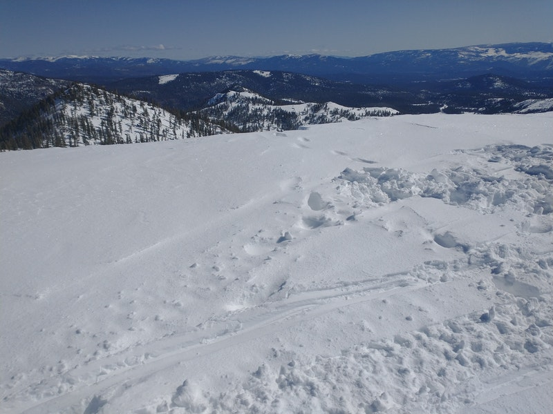 <b>Figure 1:</b> The torn up snow is where the victim parked their snowmobile. The footprints lead to the edge where the cornice broke. (<a href=javascript:void(0); onClick=win=window.open('https://caic-production.imgix.net/rj2kn8c4eqd9kiezejdeptwbr1s4?ixlib=php-3.1.0&s=7ef41c9e59f8d2796fc78d0fe29e7d35','caic_media','resizable=1,height=820,width=840,scrollbars=yes');win.focus();return false;>see full sized image</a>)