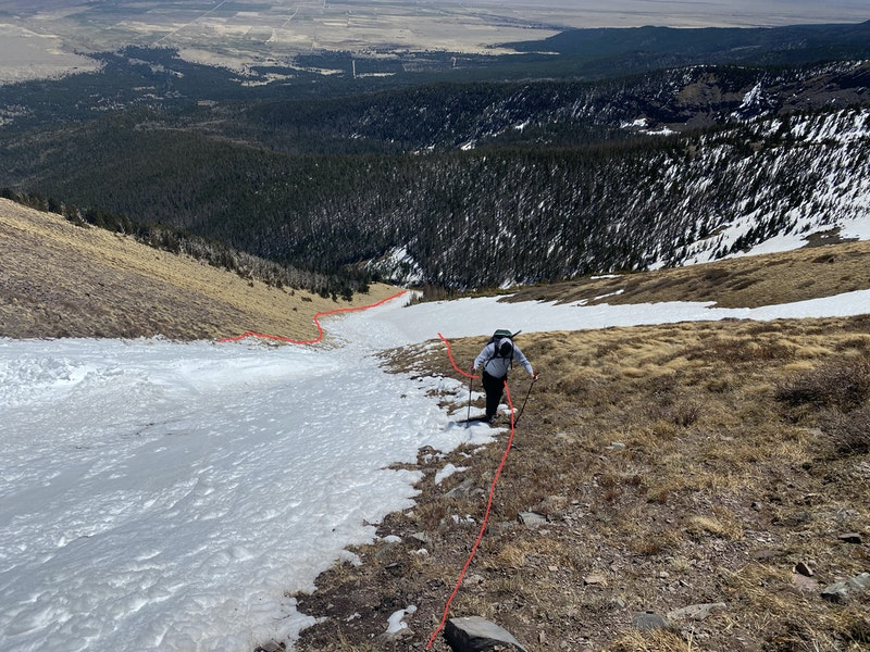 <b>Figure 6:</b> Looking down the path of the avalanche. The slide entrained wet snow as it descended. The red lines mark the approximate boundaries of the snow field before the slide. Investigators found denser snow in the center and western (left side of the image) side of the snowfield that the avalanche did not entrain. (<a href=javascript:void(0); onClick=win=window.open('https://caic-production.imgix.net/soje774v4qub6l61v96rry80linz?ixlib=php-3.1.0&s=a305d89366b37a2f2d7ca9721feec2da','caic_media','resizable=1,height=820,width=840,scrollbars=yes');win.focus();return false;>see full sized image</a>)