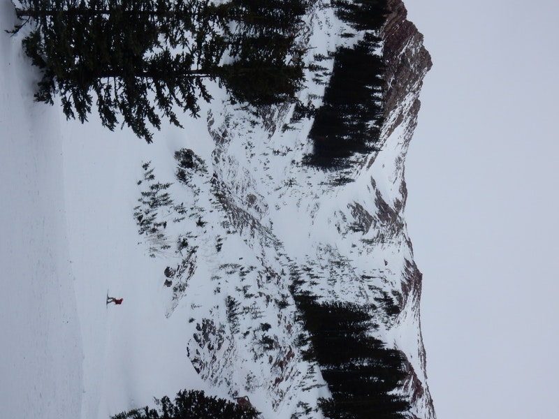 <b>Figure 8:</b> Looking up at the terrain feature and avalanche path.  Skier 2 and the debris pile ended about 100 meters up slope from the skier shown in this photo. (<a href=javascript:void(0); onClick=win=window.open('https://caic-production.imgix.net/v22jro63hvypsg2q8xvufk7rq9lj?ixlib=php-3.1.0&s=d0477f560b41cb8421b56c5b8d377414','caic_media','resizable=1,height=820,width=840,scrollbars=yes');win.focus();return false;>see full sized image</a>)