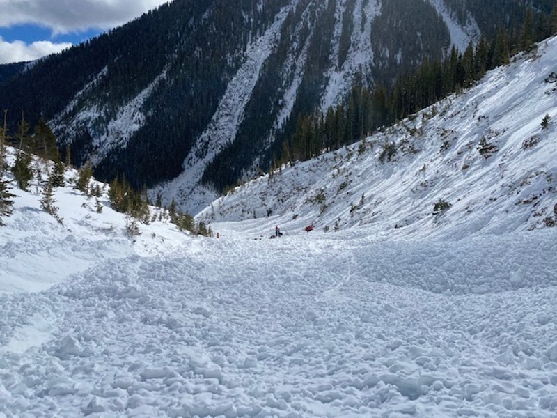 <b>Figure 6:</b> An image looking east, down the gully, from near Skier 2's burial location. Searcher's equipment is staged near the location Skier 1 was buried. (<a href=javascript:void(0); onClick=win=window.open('https://caic-production.imgix.net/w7reck8afxqd1udr6uxg6ggo5h62?ixlib=php-3.1.0&s=afba052f59d16c76541d88abad64e562','caic_media','resizable=1,height=820,width=840,scrollbars=yes');win.focus();return false;>see full sized image</a>)