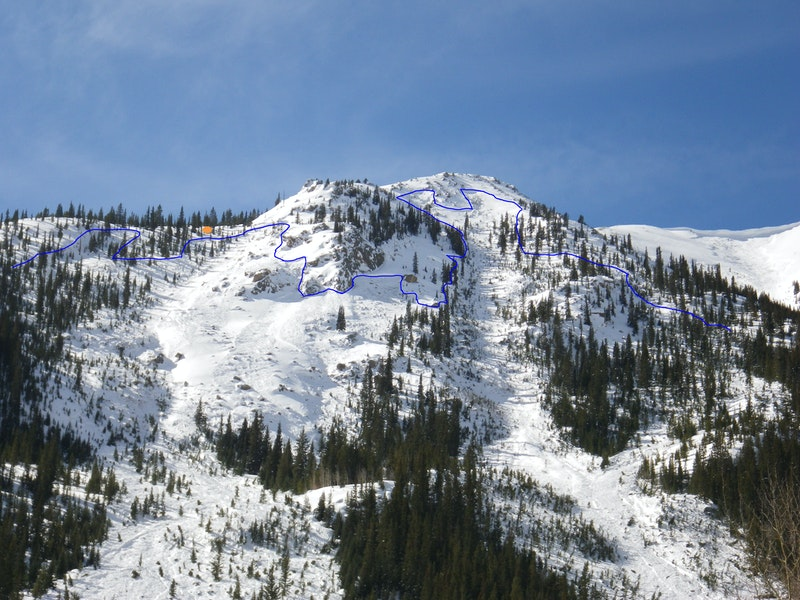 <b>Figure 32:</b> The Star Mountain A avalanche path. The blue line shows the location of the crown face from the avalanche on February 15, 2014. The orange circle is the location of the group's snowpit. The portion of the crown face that extends downhill to the viewer's left of the snowpit is where  Riders 6 and 7 were at the time of the avalanche. (<a href=javascript:void(0); onClick=win=window.open('https://caic-production.imgix.net/y5g3qjulhnwsdxn0si6puu0vqj2c?ixlib=php-3.1.0&s=99884793e7c035eb2d247156575d0146','caic_media','resizable=1,height=820,width=840,scrollbars=yes');win.focus();return false;>see full sized image</a>)